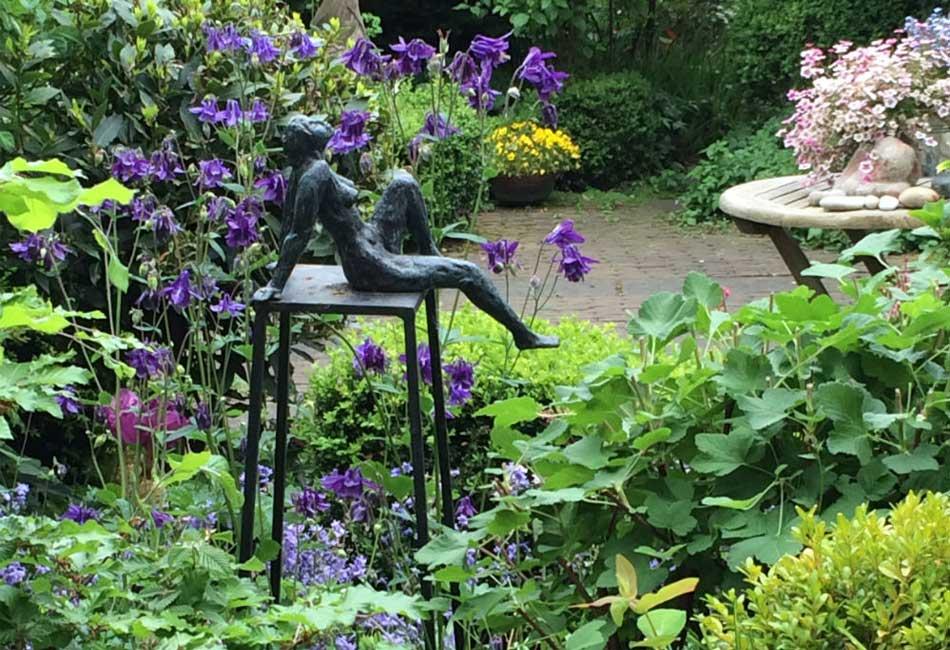 Tuin met akelei en beeld